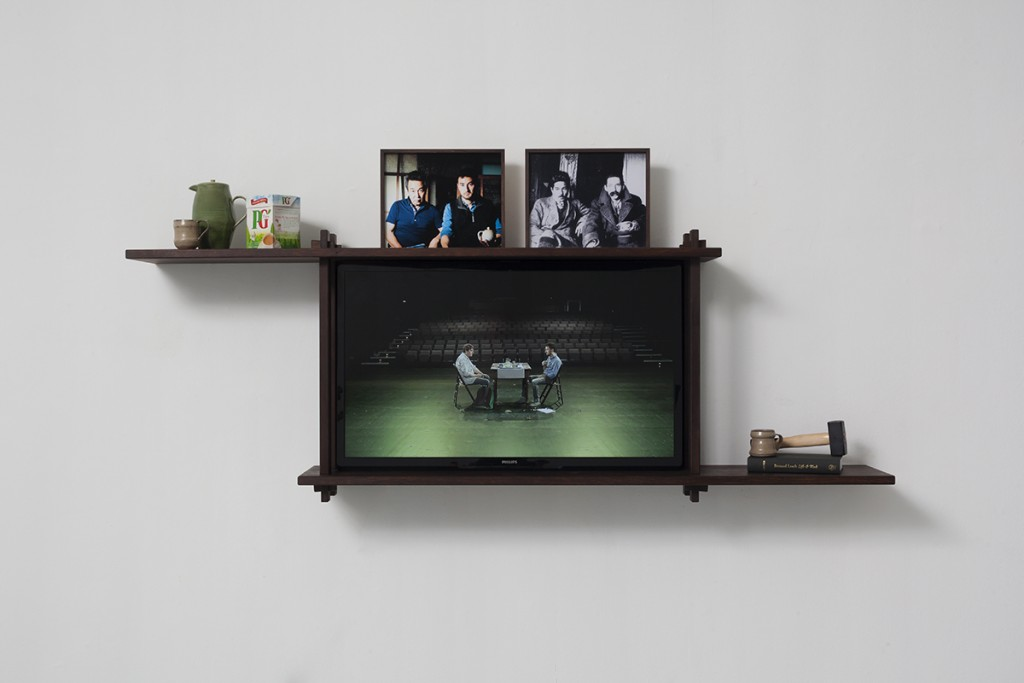 Simon Fujiwara, Rehearsal for a Reunion, 2013, wooden shelf, various objects, LCD TV screen, 73 x 205 x 30 cm