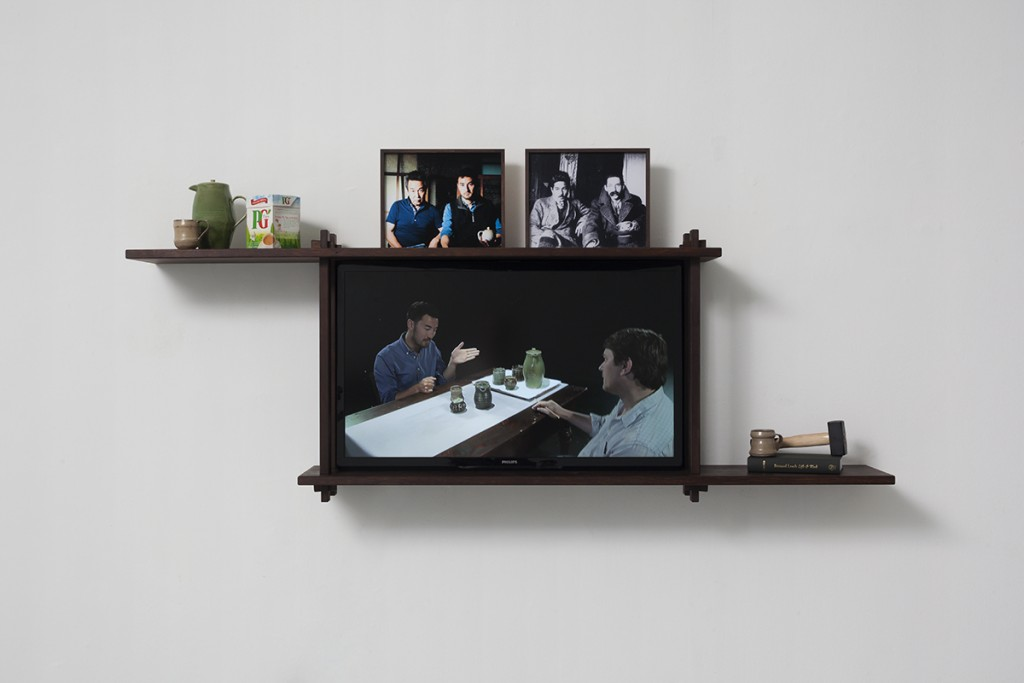 Simon Fujiwara, Rehearsal for a Reunion, 2013, wooden shelf, various objects, LCD TV screen, 73 x 205 x 30 cm, unique