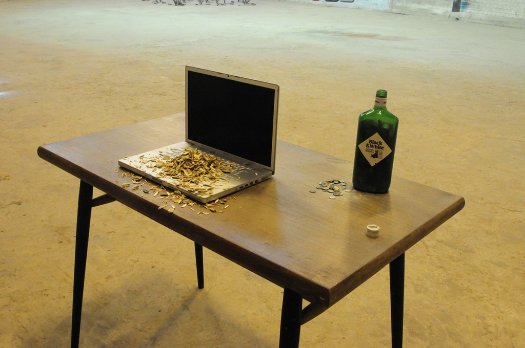 "Eli Petel, ""One Hundred Grams of Black"", 2010, table, lap-top, seeds, coins and a bottle"