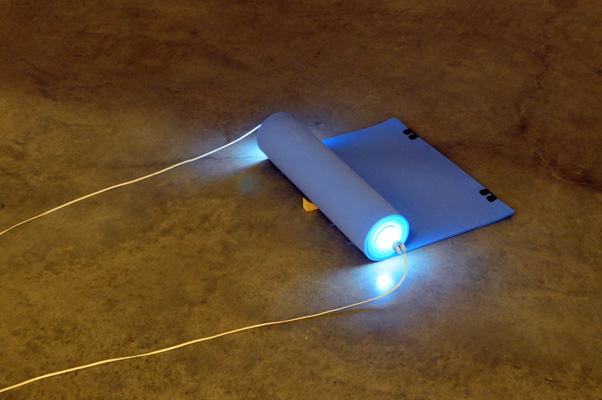 Barak Ravitz, Cylinder, 2006, rolled traveling mattress, Fluorescent light, 12x30x60 cm