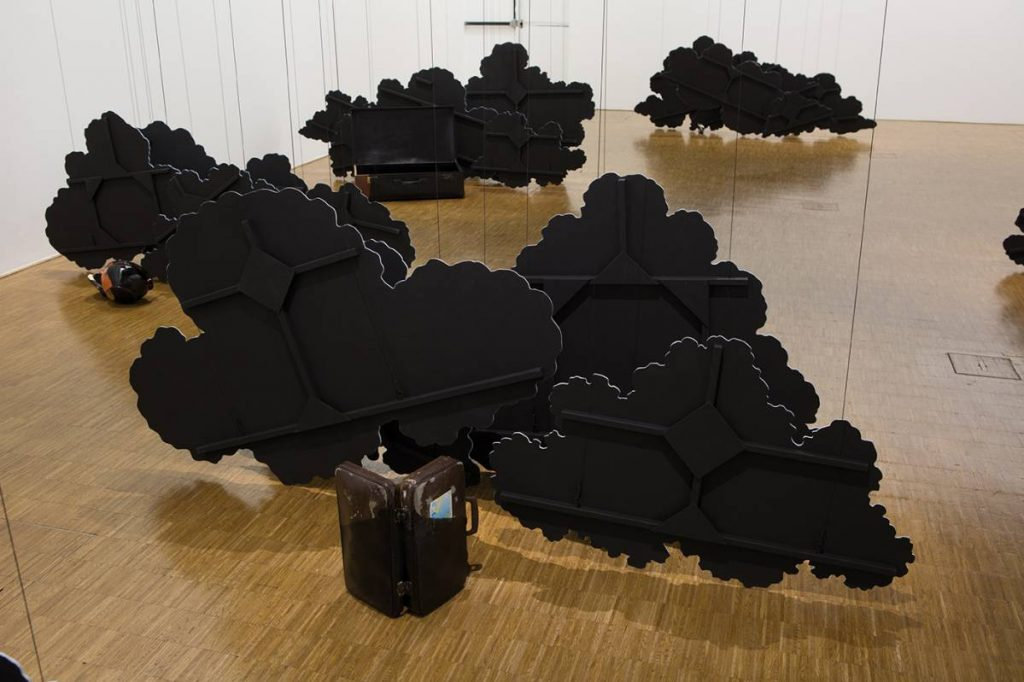 Latifa Echakhch, Inking (The pétanque balls), 2014, Wooden and steel balls, leather case, cross country championship sticker, Chinese Ink, wooden cloud scenery, canvas, acrylic paint, steel wire, dimensions variable, unique, exhibition view Centre Pompidou, Paris