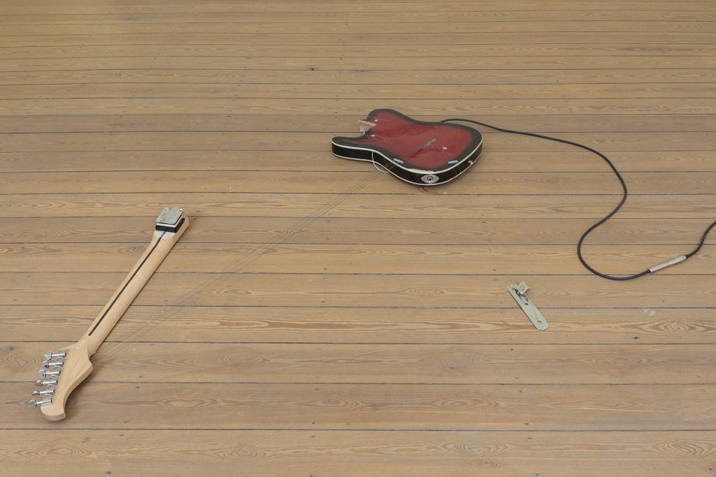Naama Tsabar, Melody of Certain Damage #6, 2018, broken electric guitar, strings, microphone, screws and guitar amplifier, 144.8 x 99 x 6.3 cm, unique