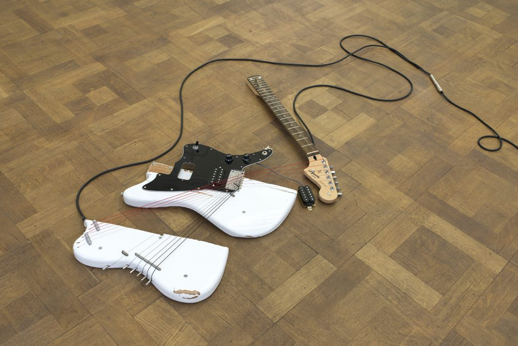 Naama Tsabar, Melody of Certain Damage #9, 2018, broken electric guitar, strings, microphone, screws and guitar amplifier, 101.6 x 58.4 x 7.6 cm, unique