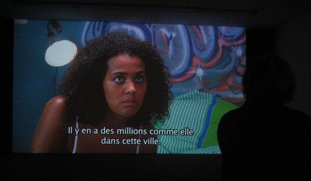 Omer Fast, De Grote Boodschap, 2007, single channel HD video colour, Flemish spoken, English & French subtitles 27 : 00 min, edition of 6 + 2 AP, installation view
