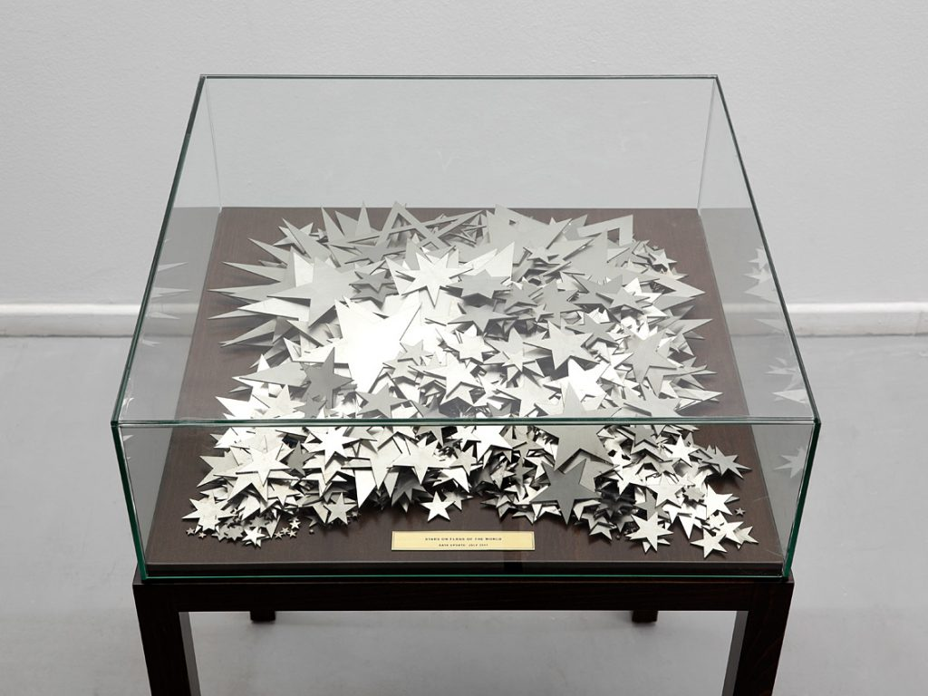 Shilpa Gupta, Stars on Flags of the World, 2012, mild Steel stars in a vitrine and an etched brass plate, 64 x 64 x 97 cm, edition 2 of 3