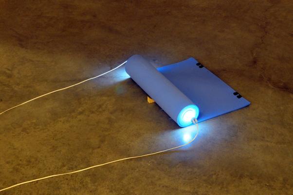 Barak Ravitz, Cylinder, 2006, rolled traveling mattress, Fluorescent light, 12x30x60 cm