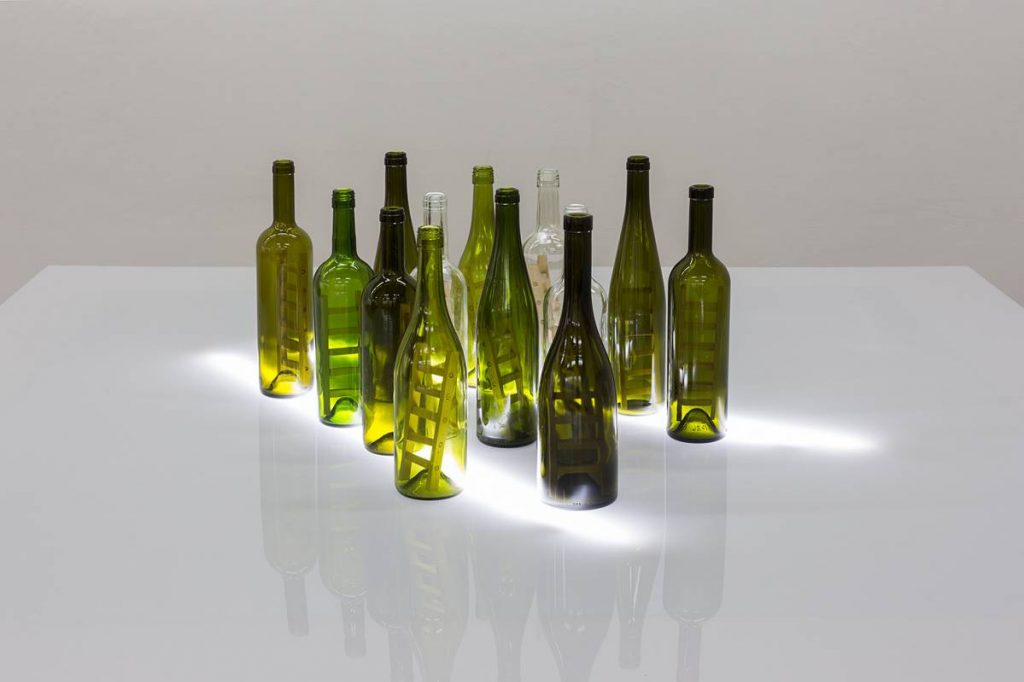 Mircea Cantor, In a moment of hesitation we become a ladder, 2016, wine bottles, wood, plexiglass, neons, 160 x 160 x 113 cm, unique