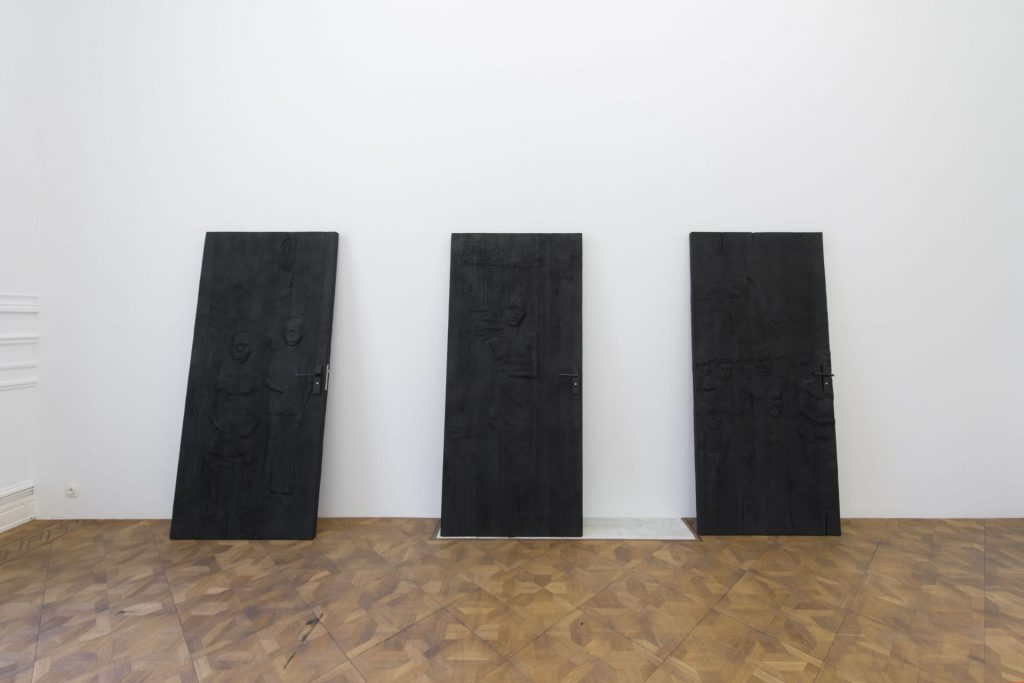 Adel Abdessemed, Feux, 2018, installation view, relief on door, carbonized, 205 x 92 x 5 cm, unique